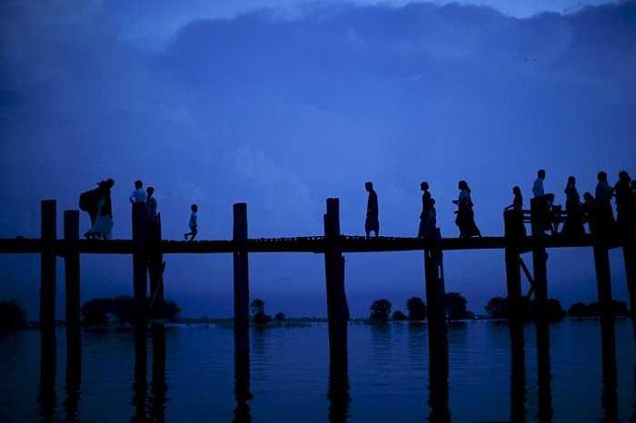 Người dân đi qua cây cầu U Bein bắc qua hồ Tuangthaman ở Mandalay, Burma