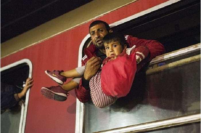 Người đàn ông di cư bế đứa trẻ lửng lơ trên cửa sổ con tàu từ biên giới Macedonia - Hy Lạp tới Serbia