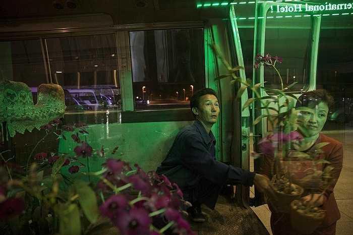 Người phụ nữ mang những bình hoa này để trang trí hành lang một khách sạn ở Bình Nhưỡng