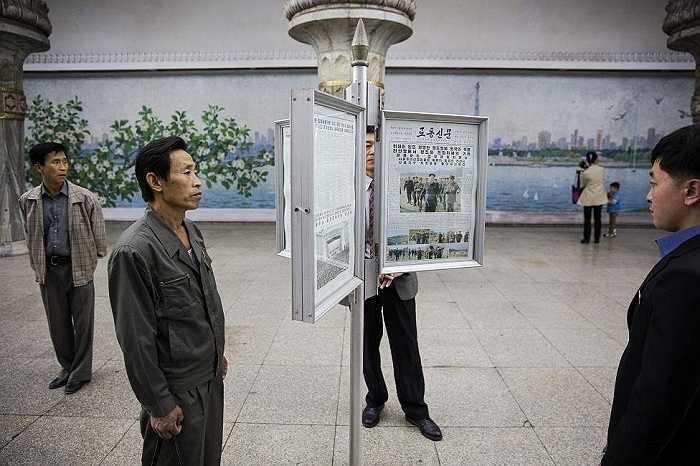 Người dân đọc báo được đặt trên các khung kính ở một ga tàu điện ngầm