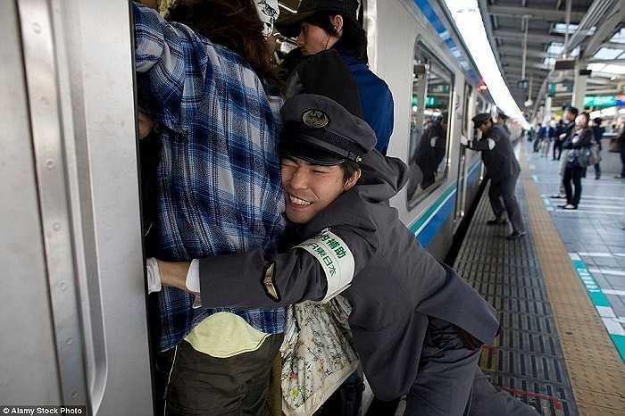 Ở các nhà ga đông đúc ở Tokyo, các nhân viên còn có thêm nhiệm vụ 'nhồi nhét' hành khách lên tàu vào giờ cao điểm