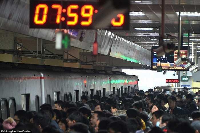 Hành khách chen chúc để lên tàu điện ngầm tại một nhà ga vào giờ cao điểm ở Bắc Kinh, Trung Quốc