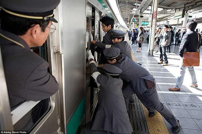 Nhiều nhân viên phải hợp sức đẩy hành khách vào trong khi cửa tàu sắp đóng