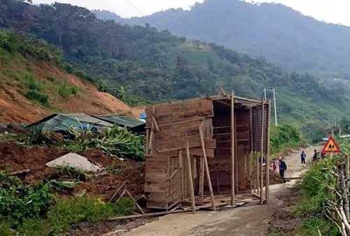 Một phần ngôi nhà truyền thống của thôn bị đất đá đẩy xuống đường. Ảnh: Phạm Trọng.