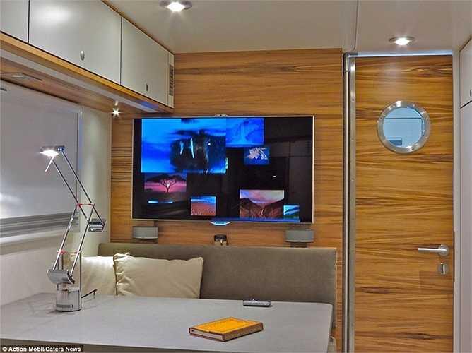 Phòng khách kiêm nơi làm việc khá đẹp mắt với TV màn hình lớn 50 inch.