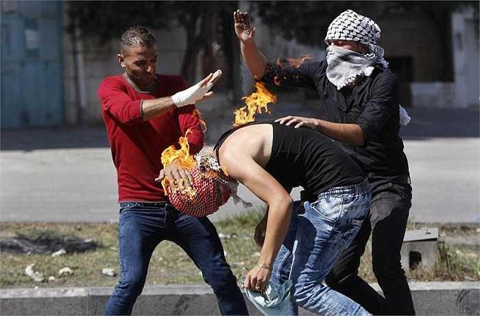 Người biểu tình Palestine dập lửa trên đầu một thanh niên trong cuộc đụng độ ở Bờ Tây, Hebron ngày 13/10