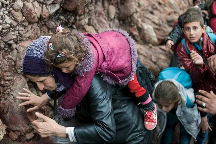 Một phụ nữ di cư cõng con gái trên lưng khi tới một bãi biển trên đảo Lesbos của Hy Lạp sau khi vượt qua Biển Aegean tới Lesbos
