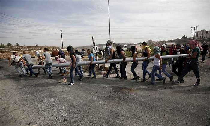 Người biểu tình Palestine mang thanh sắt lớn chắn đường trong cuộc đụng độ với quân đội Israel