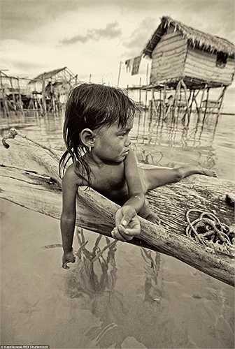 Một bé gái chơi đùa trong một vùng nước nông. Những đúa trẻ ở đây được dạy những bài học thích nghi với biển cả từ rất sớm