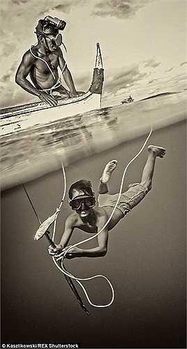 Một thợ lặn khoe dụng cụ đánh bắt của mình. Họ sống lênh đênh trên mặt biển không có chỗ ở ổn định