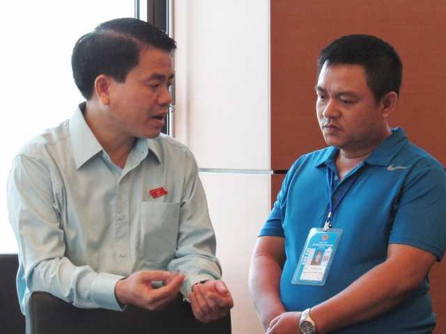Giám đốc Công an TP Hà Nội Nguyễn Đức Chung (trái) trao đổi với phóng viên bên lề họp tổ QH sáng nay. Ảnh: Chung Hoàng