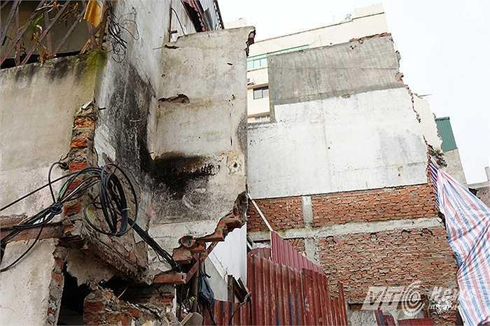 Một mảng tường vốn từng là tầng hai còn sót lại của một ngôi nhà nay vẫn ngang nhiên tồn tại lơ lửng trên đầu người đi đường và có nguy cơ sập xuống bất cứ lúc nào.