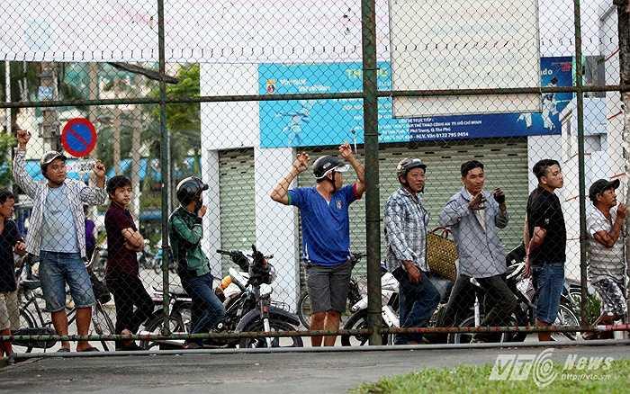 Một số khán giả đứng theo dõi trận đấu bên ngoài hàng rào.