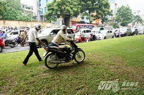 Nhiều người điều khiển xe máy còn vô ý thức dắt xe, đi xe trên thảm cỏ để tránh ùn tắc.