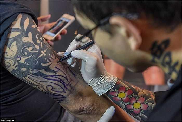 Nghệ nhân vẽ bằng bút mực trước khi dùng kim xăm
