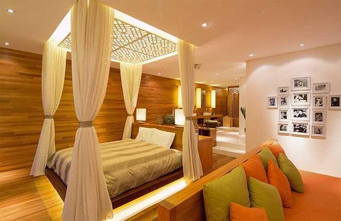 Phòng ngủ rộng thoáng và ấm áp với chất gỗ, vải, màn và đèn trang trí. Tất cả màu sắc, kiến trúc, đồ nội thất đều gắn kết chặt chẽ với nhau tạo nên một không gian hài hòa và thư thái.