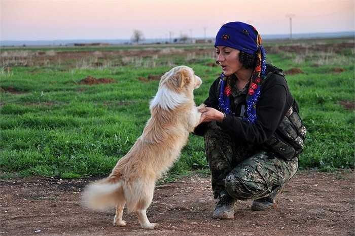 Một nữ binh sĩ người Kurd thuộc Đơn vị Bảo vệ Phụ Nữ (YPJ), đội quân tình nguyện ở Syria bao gồm toàn nữ giới , chơi đùa cùng chú chó ở thị trấn Ras al-Ain