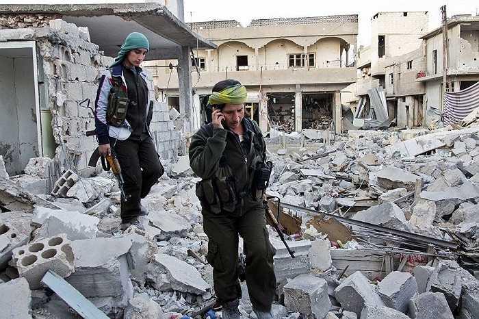 Các nữ binh sĩ người Kurd đi qua đống đổ nát ở khu vực đang tranh chấp Kobani, Syria