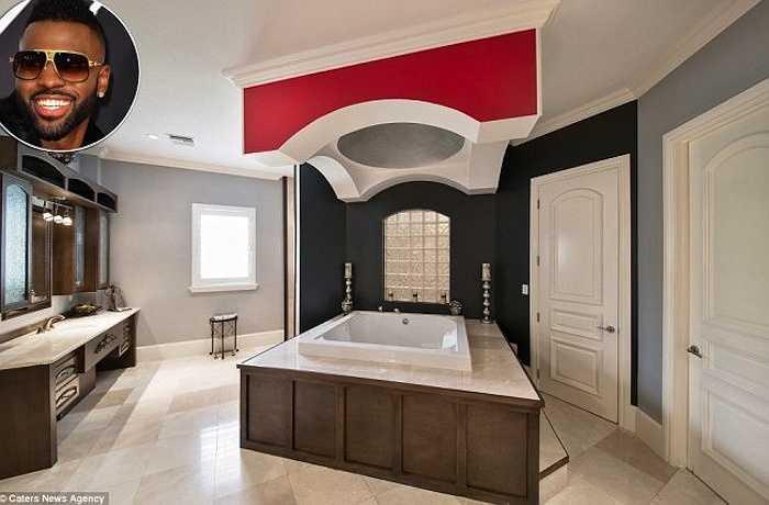 Hình ảnh phòng tắm hiện đại của ca sĩJason Derulo, 26 tuổi trong biệt thự ở Florida của anh. Phòng tắm được sắp đặt như phòng ngủ, bồn tắm lớn bao quanh bằng gỗ nằm ở giữa phòng, trang trí với màu sắc nhã nhặn,nổi bậtsự đối lập giữtrần màu đỏ và tường màu đen.
