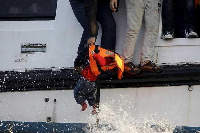 Một em bé được kéo lên thuyền cứu hộ sau khi chiếc thuyền chở 150 người tỵ nạn Syria bị chìm giữa biển Aegean. Họ từ Thổ Nhĩ Kỳ vượt biển để đến đảo Lesbos, Hy Lap ngày 30/10