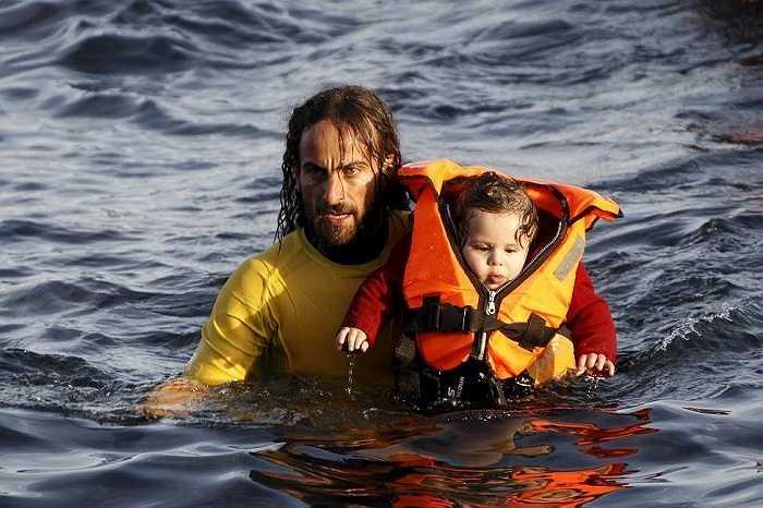 Người đàn ông đưa em bé lên thuyền cứu hộ. Những ngày gần đây, nhiều người tỵ nạn đã phải bỏ mạng trên biển do đắm thuyền