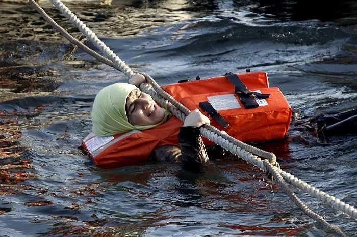 Người phụ nữ hốt hoảng bám vào dây thừng để lên thuyền cứu hộ
