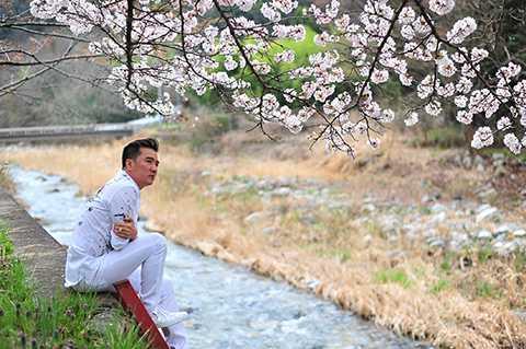 Nam ca sĩ trầm mình giữa vẻ đẹp thiên nhiên tuyệt vời của rừng hoa anh đào tại xứ sở Mặt trời mọc.
