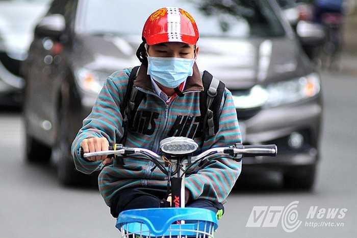 Một em học sinh trường THCS Nghĩa Tân (Cầu Giấy, Hà Nội) co ro vì gió lạnh.