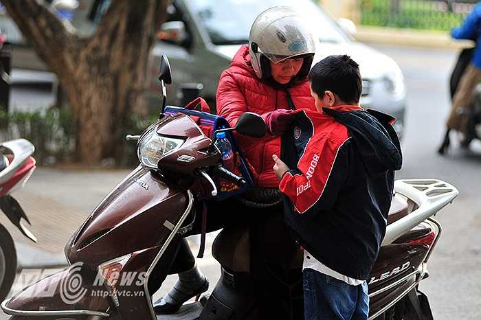 Một phụ huynh khoác thêm áo ấm và dặn dò trước khi tiễn con vào học.