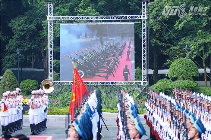 21 phát đại bác chào đón ông Tập Cận Bình được tường thuật qua màn hình lớn - Ảnh: Tùng Đinh