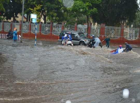 Xe và người bị nước cuốn trôi trên đường Nguyễn Tất Thành