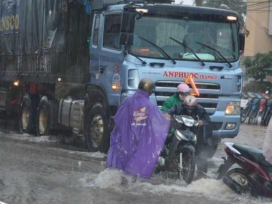 Nước chảy xiết, nhiều xe máy ngã trước đầu xe tải