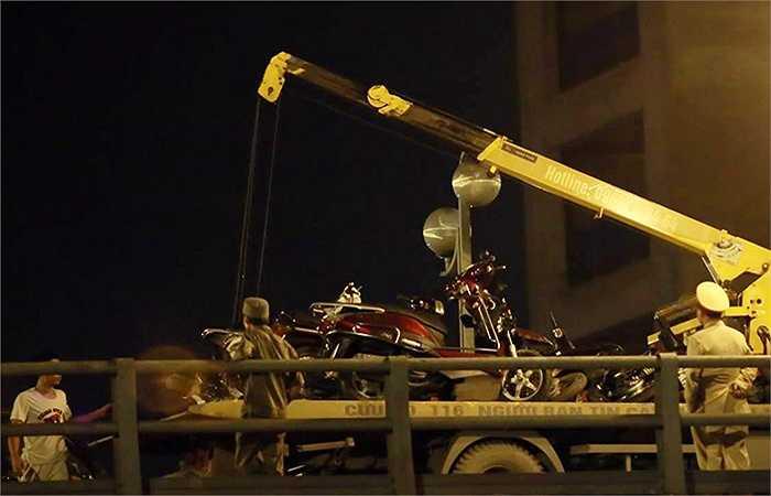 Lực lượng chức năng dùng xe cẩu chuyên dụng để di dời những chiếc xe bị hư hỏng, giải phóng hiện trường.