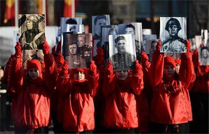 Các cháu thiếu nhi mang chân dung cha ông, những người có mặt trong cuộc diễu binh năm xưa