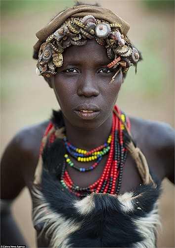 Một phụ nữ trẻ ở thung lũng Omo gần biên giới Kenya với chiếc mũ ấn tượng làm từ nắp chai