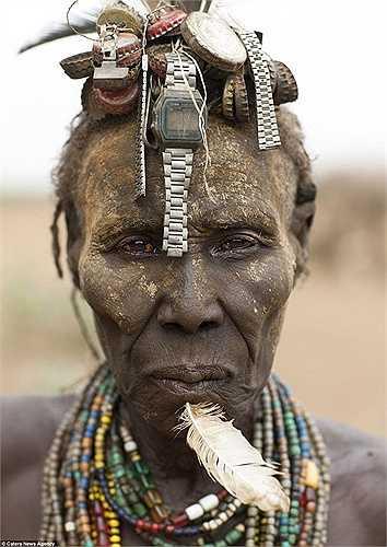 Người phụ nữ với những chiếc đồng hồ cũ trên đầu và lông vũ cắm xuyên qua cằm