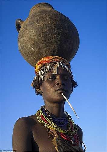 Một phụ nữ với chiếc nồi nấu rượu to trên đầu