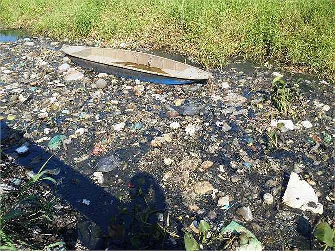 Trên dòng kênh có đủ các loại rác thải, từ một chiếc xuồng nhỏ bị hư...