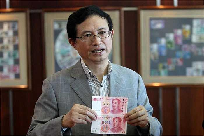 Ông Shao Guowei, Giám đốc công nghệ của công ty in ấn và đúc tiền Trung Quốc cầm tờ tiền giấy cũ so sánh với mẫu tiền mới.