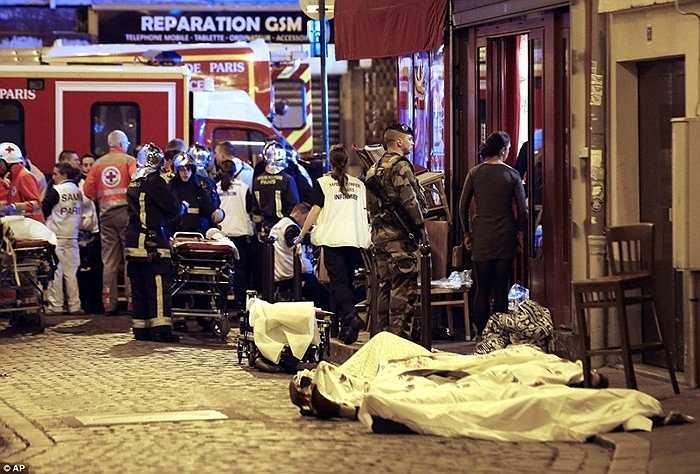 Người lính đứng bên xác nạn nhân bên ngoài nhà hàng Cambodian, quận 10 thủ đô Paris.