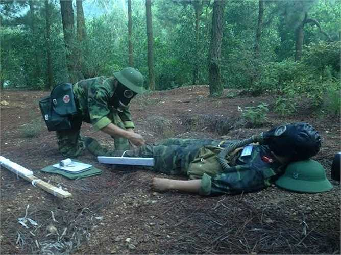 Lực lượng quân y tiến hành xử lý vết thương khu vực có độc. (Nguồn: Báo Quân đội nhân dân)