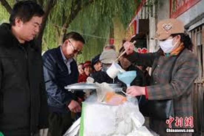 Sữa sau khi lấy được đựng trong bình inox để bán cho khách. Hàng trăm khách mua sữa cầm theo chai đứng chờ đợi đến lượt mỗi sáng