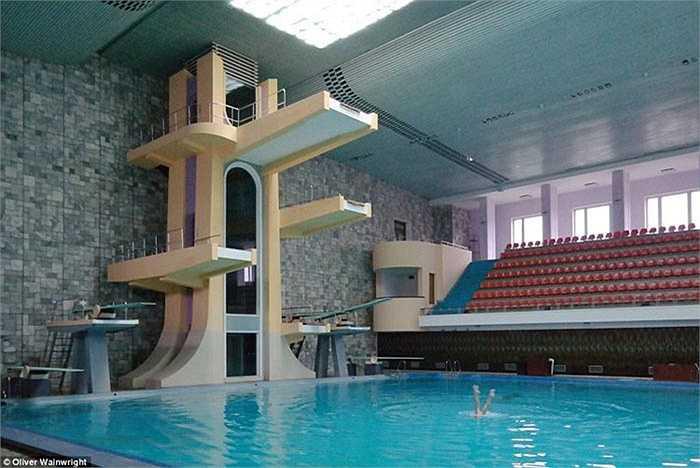 Hồ bơi lớn có màu pastel nhẹ nhàng, khán đài đối xứng theo kiểu sân vận động.