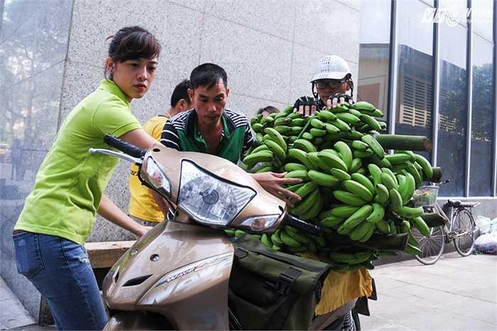 Nhân viên kênh VTC16 giúp người vận chuyển buộc chuối lên xe trước khi giao cho khách hàng