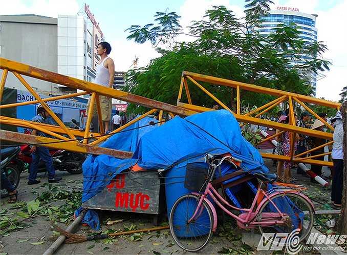Thân cần cầu đổ đập xuống qua hàng rào sắt bảo vệ công trường, đè vào đống đồ đạc, hàng hóa của người dân để bên lề đường.