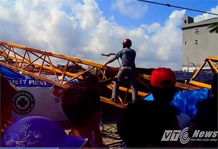 Quá đau đớn, một người đàn ông cầm khúc cây định trèo qua hàng rào sắt vào công trường 'tính sổ', rất may được mọi người can ngăn.