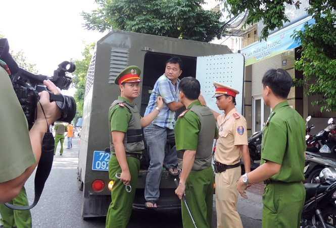 Nguyễn Thành Nam bị bắt đưa lên xe - Ảnh: Đ.Hà