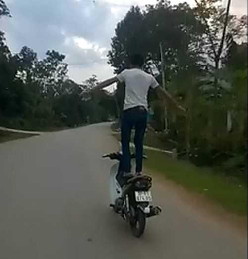 Nam thanh niên đứng cả hai chân trên yên xe, hai tay dang ngang khi xe đang chạy