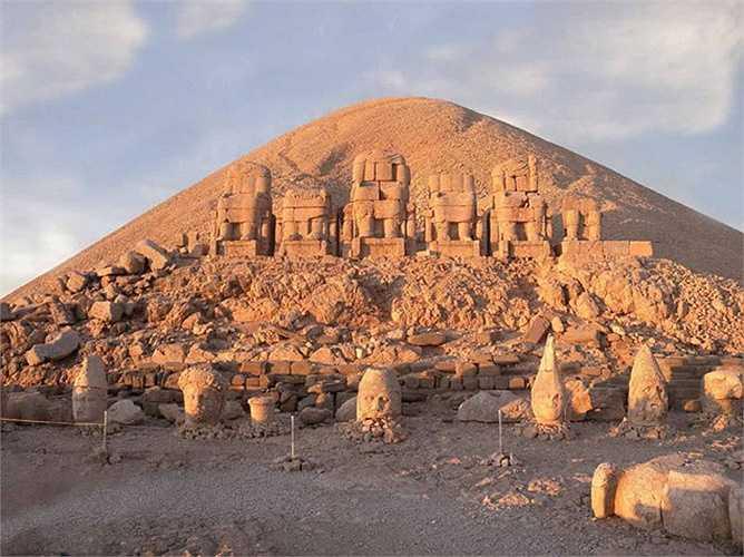 Phía sau các bức tượng là một lăng mộ khổng lồ hình nón có đường kính 152 m và cao 49 m, thoạy nhìn trông như một quả núi.