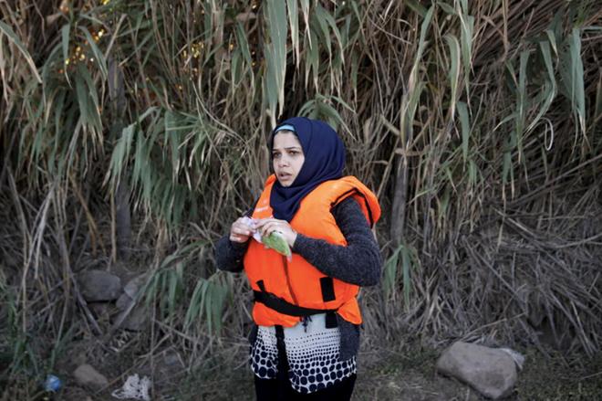 Một người tị nạn Syria mở túi bóng dùng để bọc điện thoại ngay sau khi đặt chân đến đảo Lesbos (Hy Lạp). Ảnh: Cnet.